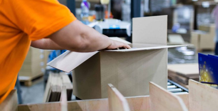 Close up shot of worker's hand preparing carton for printing in a modern printing house.
